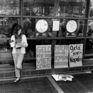Junge Frau an Fensterfront lehnend