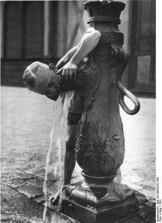 Junge trinkt aus Wasserpumpe